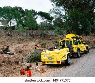 Mallorca, Baleares, Spain - May 10, 2018: Land Rover yellow Jeep SUV parked on a forest road with Incendis Forestals Fire Forest protection with team of workers eating lunch near the road