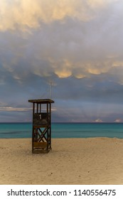 Mallorca, Glowing sky cloud formations over lifeguard house at sand beach at dawn