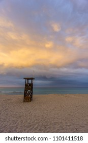 Mallorca, Orange shiny cloudscape at beach over lifeguard house at dawn