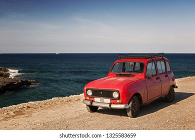 MALLORCA / SPAIN - 24/08/2014 vintage retro red renault 4 car on a sandy beach road with dark blue sea water, rocks, cliffs, stones, a sailing clipper boat on the horizon, a blue sky and white clouds