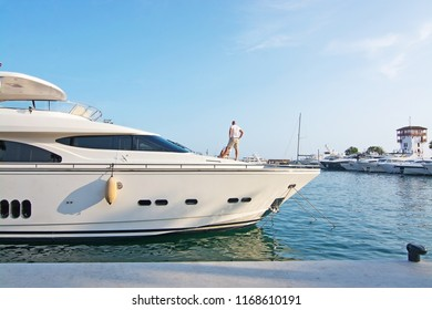 MALLORCA, SPAIN - AUGUST 30, 2018: Man on deck of luxury yacht in Puerto Portals marina on a late summer sunny afternoon on August 30, 2018 in Mallorca, Spain
