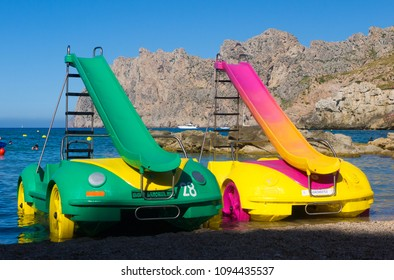 Mallorca, Spain - July 6, 2017: Two brightly coloured pedalos parked on a beach by the water's edge in Cala San Vicente.