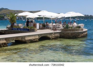 Mallorca, Spain - July 7, 2017: Patrons enjoy a seaside view as they eat at the Capri Bar & Restaurant in Port de Pollenca.