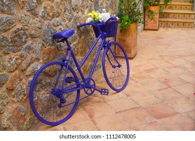 Mallorca, Spain - June 24, 2017: A purple bicycle leans against a stone wall in the village of Deia.