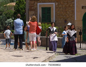 Mallorca, Spain - June 24, 2017: A tourist in the town of Deia raises her camera as local girls dressed in traditional clothes walk past.