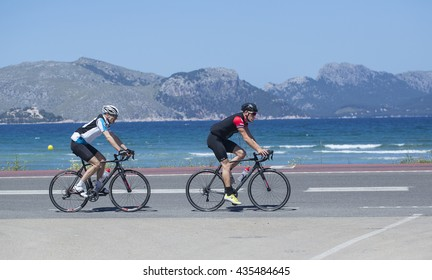 Mallorca, Spain -  May 4, 2016: Cyclist passes a typical beach  on the boardwalk at Alcudia Beach.