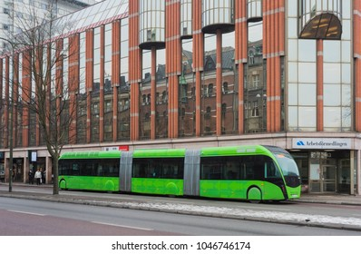 MALMO, SWEDEN - MARCH 07, 2018: The new environmentally friendly local bus, driven by clean Power, in front of a new building in Malmo city