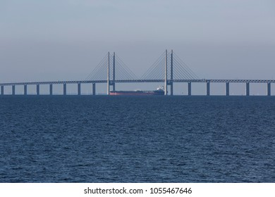 MALMO, SWEDEN - MARCH 19, 2018: A tanker is passing below the highest point of the Oresund bridge between Copenhagen Denmark and Malmo Sweden