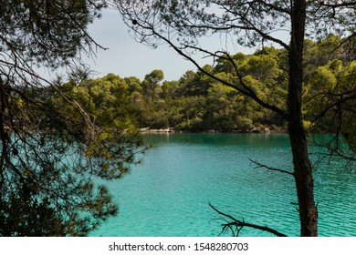 Malo Jezero turquoise bright colored saltwater lakes at the National Park on the island Mljet, Croatia. Mediterranean coast with greenery creating a calm scene, UNESCO protected