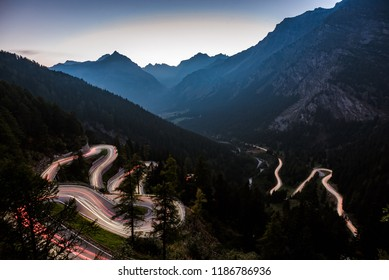 Maloja Pass road - Night view of Maloja Pass road serpentine in Switzerland shined with car light trails.