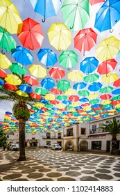 Malpartida de Caceres, Spain - May 30, 2018: Multi-colored umbrellas background. Colorful umbrellas floating above the street. Street decoration.