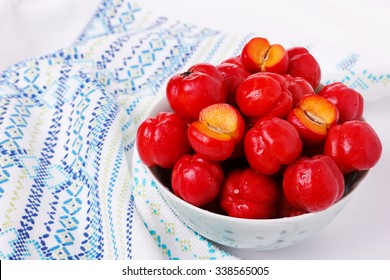 Malpighia glabra (red acerola), tropical fruit in bowl on white background. Selective focus
