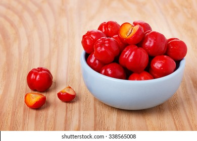 Malpighia glabra (red acerola), tropical fruit in bowl on wooden table. Selective focus
