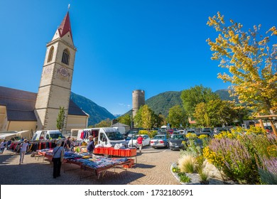 Mals, Italy - September 18, 2019: Tourists flock the market stalls on a square in the Italian village of Mals (Italian: Malles), situated in the valley Val Venosta in the region of Alto Adige (Italy)