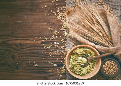 Malt and hop in wooden pots and rye ears on burlap cloth on brown wooden table background with copy space.