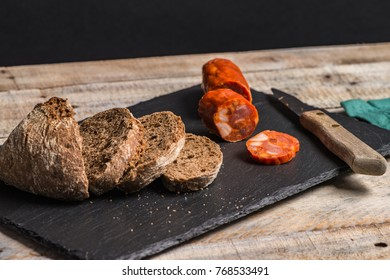 Malt loaf bread and chorizo slices on table.