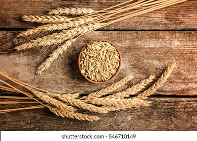 Malt in small bowl and spikes on wooden background