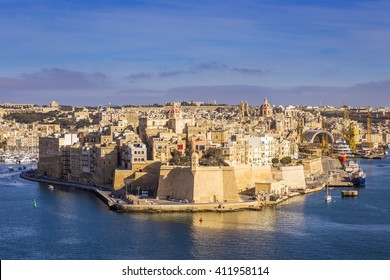 Malta - Aerial view of the ancient walls of Senglea and Gardjola Gardens shot from Valletta on a sunny day with blue sky