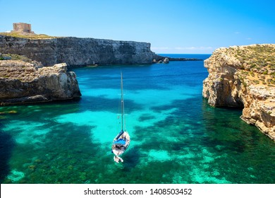 Malta. Crystal lagoon of Comino island with yacht. Scenic summer tropical landscape. Clear bay with cliffs and transparent water. Travel destination scene.