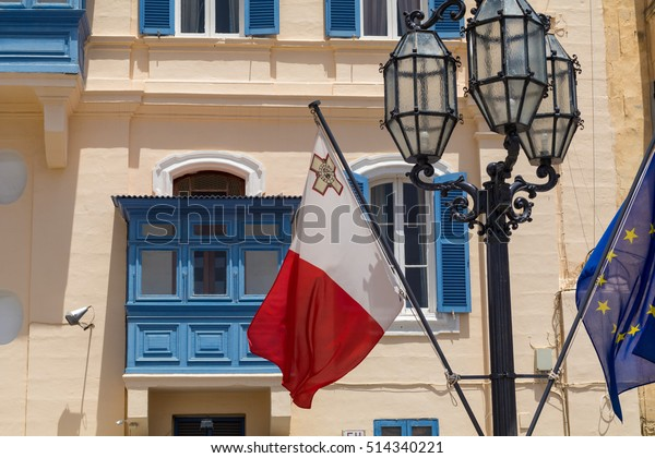 Malta and EU flag in front of traditional Maltese blue balcony's, with old lampost, Valletta, Malta