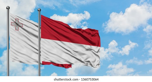 Malta and Indonesia flag waving in the wind against white cloudy blue sky together. Diplomacy concept, international relations.