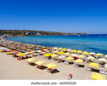 Malta, Mellieha Bay  beach, June 2017. Picture is showing sun umbrellas at Mellieha Bay beach with hotel  in the background.