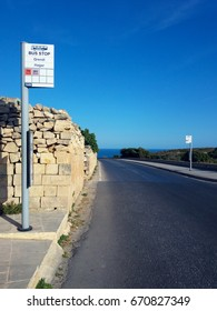 Malta road and bus stop pole with blue sky and sunny day. Public transport to Hagar