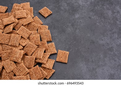 Malted shredded wheat biscuits breakfast cereal in a border line with copy space on a dark grey slate tile background