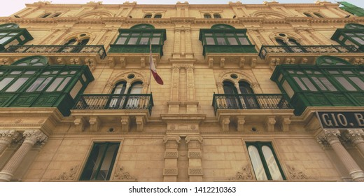 Maltese Baroque Architecture, Low Angle Facade Old Building with Green Balcony and Decorated Stonework, Summer 2018 horizontal photography