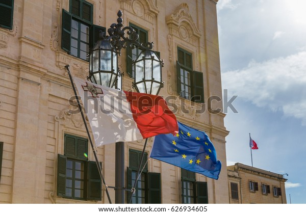Maltese and European Union EU Flag flying, in front of beautiful Auberge de Castille, the office of the prime minister of Malta, with traditional lamp post, Valletta, Malta, March 2017