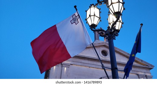 Maltese flag on flagpole at night in Valletta - capital city of Malta. Malta flag in front of evening blue sky.