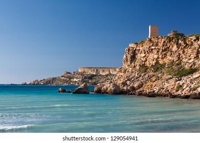 Maltese rocky seascape and Ghajn Tuffieha Tower, Riviera Bay, Malta