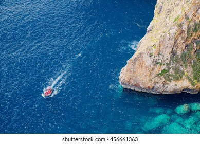 Maltese seacoast near the Blue Grotto area with steep rocks and clear blue water, a typical boat with tourists floats around.