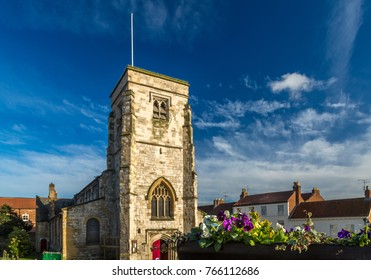 Malton Yorkshire and St Micheal's Church with flowers in the foreground during summer