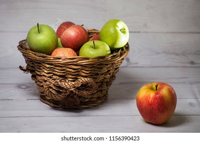 Malus domestica- Red and green apple fruits (Malus domestica) in wicker basket on white wooden background.