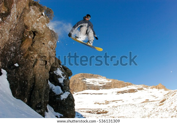 MALUTI MOUNTAINS, LESOTHO - 2 JULY 2014: A snowboarder jumps off a cliff in rural Lesotho. Lesotho is a landlocked country within South Africa & is known for its mountainous terrain. Editorial.