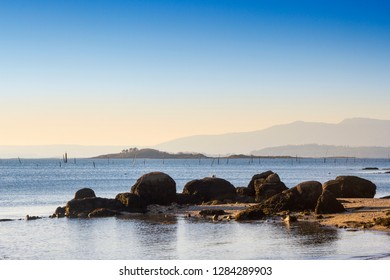 Malveiras islands in Arousa estuary with the wooden poles noting the clam hatcheries arising from the sea