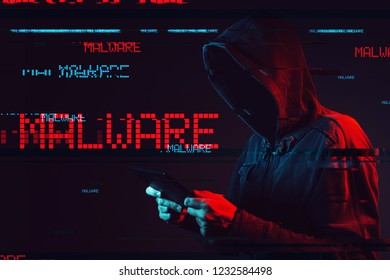 Malware concept with faceless hooded male person using tablet computer, low key red and blue lit image and digital glitch effect
