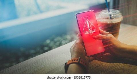 Malware,cyber crime and (PDPA)Personal Data Protection Act concept.Close up hand of anonymous hacker and uses a malware with smartphone to hack password the money from Bank accounts and personal data.