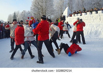 "Malye Korely, Arkhangelsk region, Russia, February, 18, 2018. People celebrating of Shrovetide in Malye Korely. Fist fight ""Wall to wall"" in front of the snow fortress"