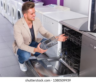 Mam selecting modern dishwasher in hypermarket and smiling