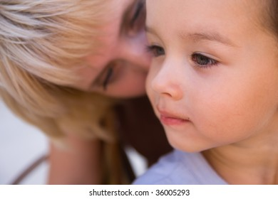 Mam to whisper in son's ear. Focus on child.