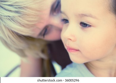 Mam to whisper in son's ear. Focus on child. Special processing