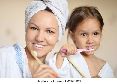 Mama and her little daughter brushing their teeth