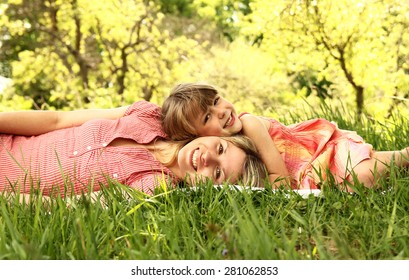 a Mama and her little daughter lie on the grass