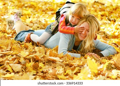 Mama and her little daughter lying on the leaves in autumn