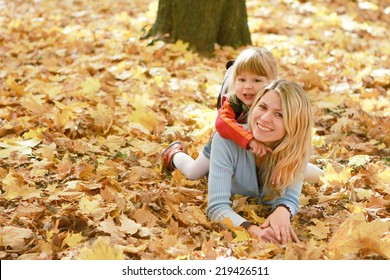Mama and her little daughter on autumn leaves