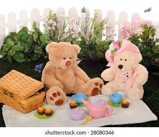 A mama, papa and baby Teddy bear having a picnic with a child's tea set.