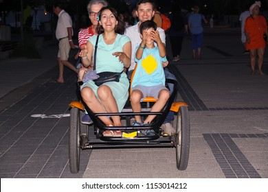MAMAIA, ROMANIA - JUNE 24, 2018: People ride a rented four-wheel bike (quadricycle) together in the evening and have fun on the cliff of Mamaia