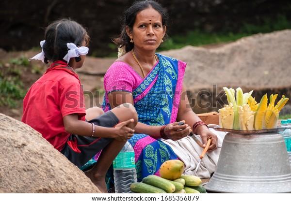 Mamallapuram, Tamil Nadu, India - August 2018: A candid portrait of an Indian woman selling corn at a tourist site in Mahabalipuram.